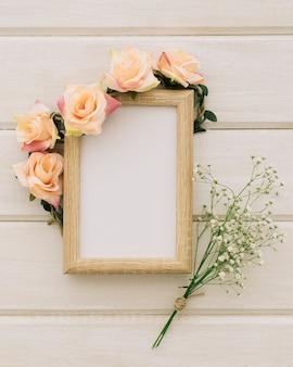 Moldura de madeira com ornamento floral e buquê de flores