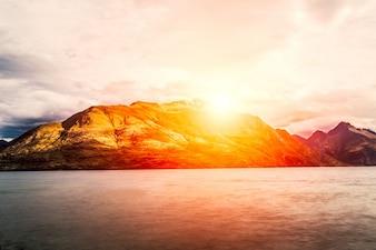 Montanhas com um grande sol