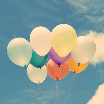 Muitos balões coloridos no céu azul, conceito de amor no verão e namorados, lua de mel de casamento. Imagens de estilo de efeito vintage.