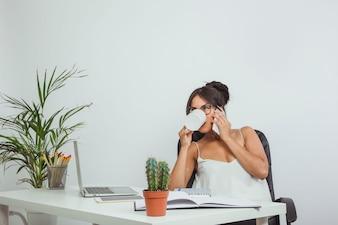 Mulher adulta bebendo café no trabalho