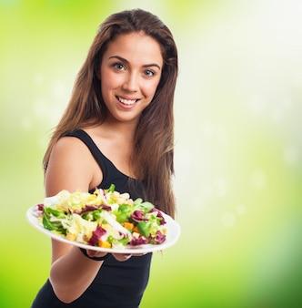 Mulher agradável que prende um prato de salada