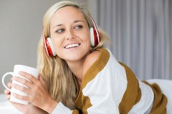Mulher alegre em fones de ouvido descansando em casa