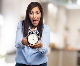 Mulher amedrontada com o relógio nas mãos