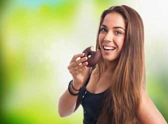 Mulher amplamente sorridente com um donut