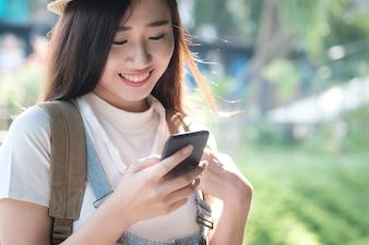 Mulher anda no parque ao ar livre e usa celular