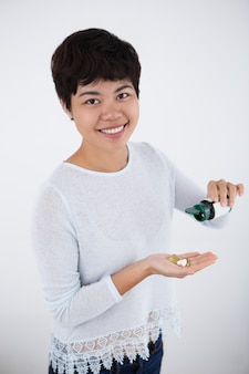 Mulher asiática feliz que derrama comprimidos da garrafa