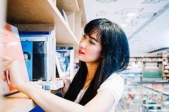 Mulher asiática que procura livros