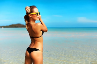 Mulher atrativa com maiô preto e óculos de sol amarelos