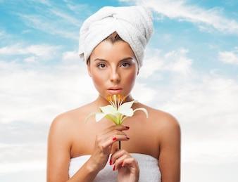 Mulher atrativa na toalha com flor de lírio frágil