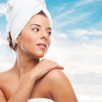 Mulher atrativa na toalha que olha por cima do ombro