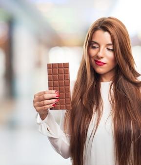 Mulher atrativa que prende uma barra de chocolate