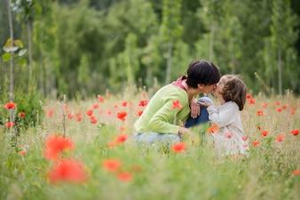 Mulher beijando sua linda filha ao ar livre