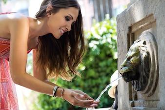 Mulher bonita bebe água da fonte no parque da cidade do verão.