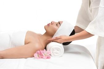 Mulher bonita que recebe tratamento de massagem no spa no salão de beleza de beleza