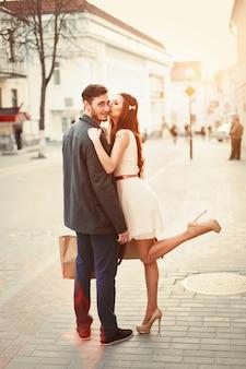 Mulher brincalhão beijando a bochecha de seu parceiro
