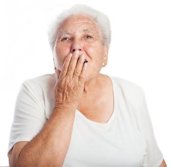 Mulher cobrindo a boca ao bocejar