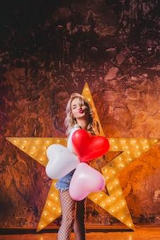 Mulher com balões enviando beijo de ar