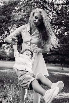 Mulher com cabelo comprido balança seu filho no parque