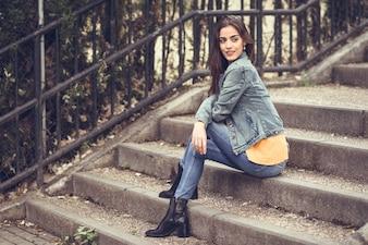 Mulher com cabelos lindos com roupas casuais em etapas urbanas.