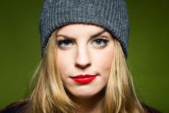 Mulher com lábios vermelhos e um boné