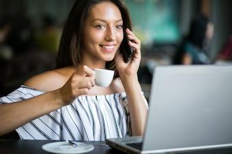 Mulher com laptop trabalhando em um café
