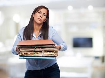Mulher com lotes de papéis e pastas