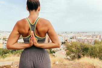 Mulher com mãos de oração nas costas