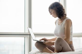 Mulher com os pés cruzados e um laptop