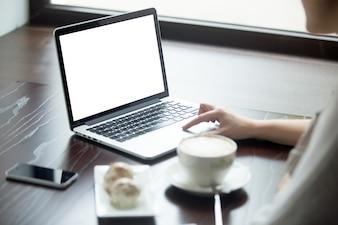 Mulher com portátil em uma mesa de madeira