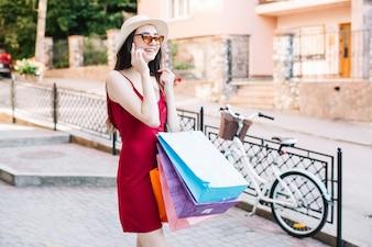 Mulher com sacos de papel falando no telefone