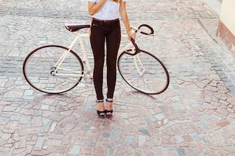 Mulher com saltos altos segurando uma bicicleta