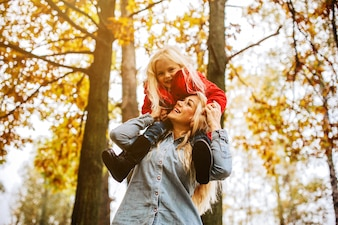 Mulher com sua filha pequena em seus ombros