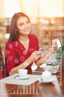 Mulher com um café e um cartão de crédito