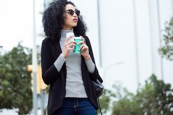 Mulher com um café e um telefone