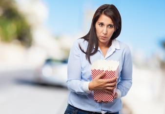 Mulher com um pacote de pipoca