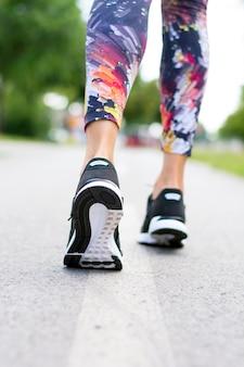 Mulher com um par de sapatos atléticos indo para correr ou correr