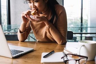 Mulher comendo no local de trabalho