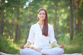 Mulher concentrada que meditating na natureza