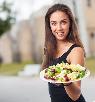 Mulher de boas-vindas com um prato de salada