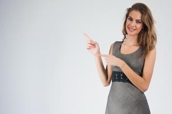 Mulher de negócio de sorriso que aponta o dedo no espaço da cópia. Retrato isolado