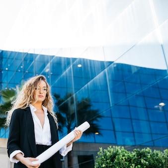 Mulher de negócio na frente do plano de exploração de construção de vidro