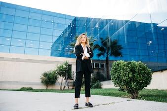 Mulher de negócios à moda em frente ao edifício de vidro