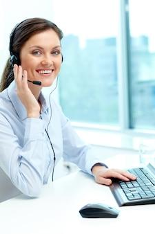 Mulher de negócios com auriculares que fala a alguém online