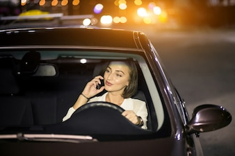 Mulher de negócios com o telefone no carro