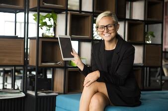 Mulher de negócios positiva que mostra o comprimido digital
