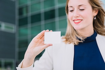 Mulher de negócios que olha o cartão de visita