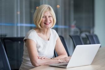 Mulher de negócios sênior alegre trabalhando no escritório