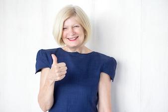 Mulher de negócios sênior bem sucedida que mostra os polegares para cima
