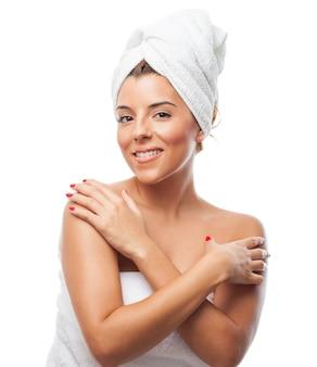 Mulher de sorriso na toalha branca que abraça-se