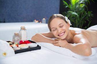 Mulher deitada na sala de massagem com uma bandeja de aromas